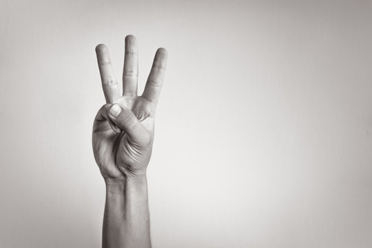 Hand showing three fingers.