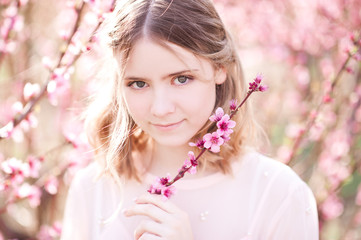 Smiling girl holding flowers in peach orchard. Looking at camera. Spring time.