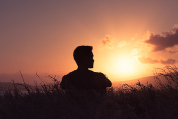 Man watching the sunrise. New day and personal reflection concept.
