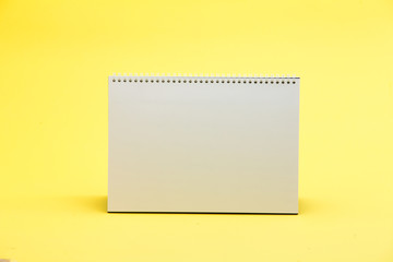 Blank white table calendar on yellow background