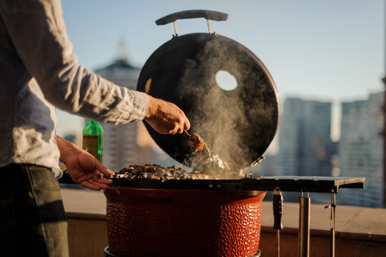 Man cooking a dish in a barbecue grill equipped with cooking tools standing on the roof