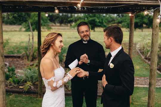 Bride and groom exchanging wedding vows on wedding ceremony