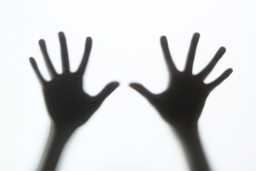 Hands silhouette behind a glass