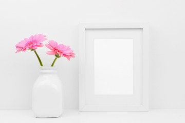 Mock up white frame and pink daisy flowers in vase on a shelf or desk. White color scheme. Portrait frame orientation.