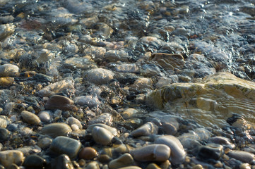 pebble stones on the sea beach, the rolling waves of the sea with foam