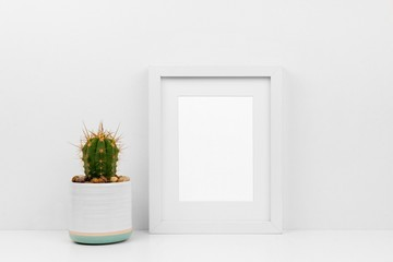 Mock up white frame and cactus in pot on a shelf or desk. White color scheme. Portrait frame orientation.