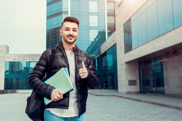 Arabian student showing thumb up holding copybooks by modern university. Happy young man successful in education.