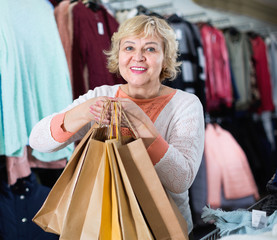 Woman consumer in the dress boutique among clothes with paper bags