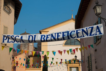 Italian charity raffle banner in charming village during parish festival with colorful flags and blue sky background. Fundraising concept.