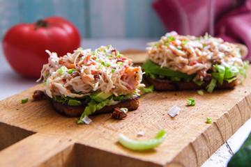 Bruschetta with crab salad served on wooden board