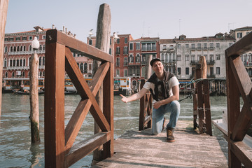 Venice, Italy. April 10, 2018. Young man exploring Venice. Sitting by the canals watching gondolas passing by near San Marco square as well as Rialto bridge.