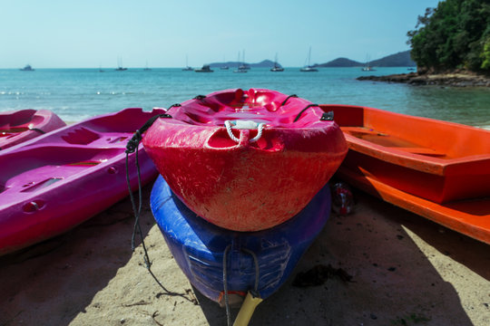 Red and blue boats among the other kayak on the the seacost in Thailand. Parking for kayaking. Summer sport activities outdoor. No people.