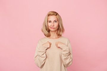 Indoor shot of pretty young woman feels happy, keep her hands on her chest and flirts fith a new friend. Isolated over pink background