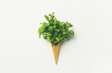 Flat-lay of waffle sweet cone with fresh leaves mint over white background, top view, horizontal composition. Spring or summer mood concept