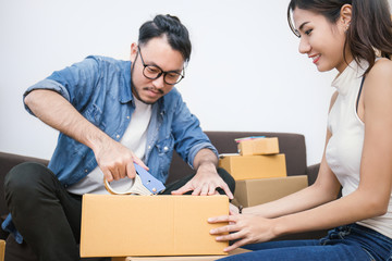 Young asian man and woman taping up a cardboard box in the office SME e-commerce business, relocation and new small business concept, SME concept
