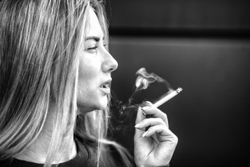 A young pretty girl smokes a cigarette in the street in the spring. Black and white.