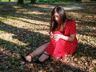 Beautiful young woman in red dress sitting in tree's shadows on ground in forest park. Outdoor fashion portrait of glamour young Chinese stylish lady. Emotions, people, beauty and lifestyle concept.