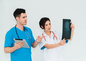 Couple doctors discussing and looking x-ray in a clinic or hospital