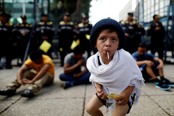 A migrant boy from Central America, moving in a caravan through Mexico, sucks a lollipop during a demonstration outside the U.S. Embassy in Mexico City