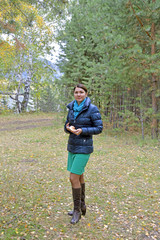 Cute, young woman is walking in the autumn forest
