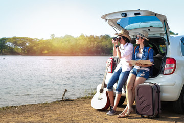 Couple of traveler sitting on hatchback of car and enjoying for view of nature near the lake during holiday.Young couple tourist have a guitar and baggage taking photo on vacation.
