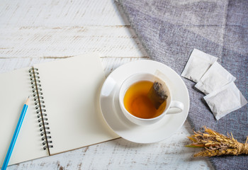 A cup of hot herbal tea with note book on white wooden table.