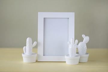 Interior frame mockup.Minimalist framed art. Minimalist picture frames idea. Empty Frame Mockup with white ceramic cactus  set on a  yellow background.