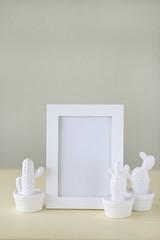 Interior  mockup.Minimalist framed art. Minimalist picture frames idea. Empty Frame Mockup with white ceramic cactus  set on a pale yellow background.
