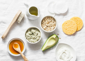 Ingredients for moisturizing, nourishing, anti-aging wrinkle face mask - avocado, olive oil, oatmeal, natural yogurt on light background, top view. Homemade beauty products concept