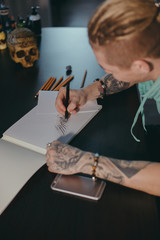 The hands of a master calligrapher. Tattoo artist the artist makes a sketch, sitting at a table in the Studio top view