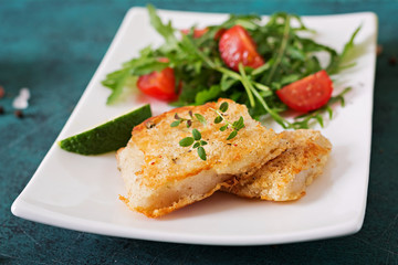 Fried white fish fillets and tomato salad with arugula.
