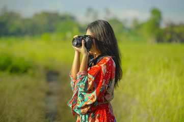 sweet young Asian Chinese or Korean woman on her 20s taking picture with photo camera smiling happy in beautiful nature landscape in holidays