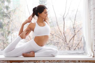 Young fit pretty woman wearing white sport cloth doing yoga exercises in class, sitting in asana eka pada radzhakapotasana (One-Legged King Pigeon Pose). near a window with white brick wall. Beautiful