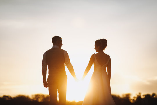 Silhouette of a newlywed couple in the sun. The bride and groom hold hands, and between them the sun shines.