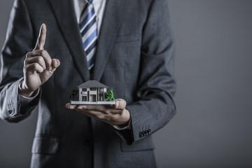 住宅模型を持っているビジネスマン