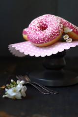 Donuts mit Himbeerglasur und weißen Zuckerstreuseln
