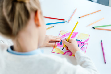 selective focus of kid drawing greeting postcard for mother with colorful pencils at table, mothers day holiday concept