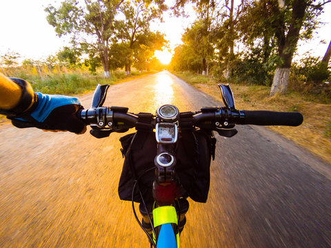 Bicycle handlebar with a speedometer and a clock in the rays of the setting sun