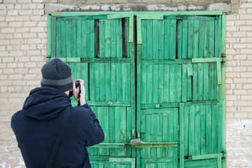 A man takes a picture of an old green wooden garage doors. Selective focus