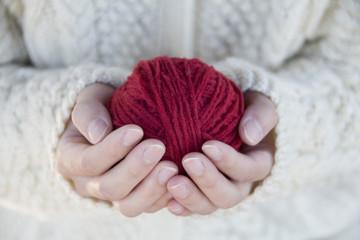 毛糸玉を持つ女性の手