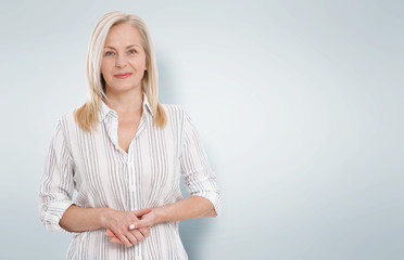 Attractive middle aged woman with folded arms on grey background