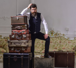 Man with beard and mustache packed luggage, white interior background. Macho elegant on tired face, exhausted at end of packing, leans on pile of vintage suitcases. Move out and relocation concept.