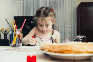 Cute little girl draws with colored pencils at home
