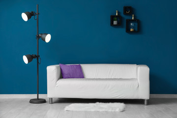 Beautiful sofa and lamp near color wall