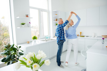 Side view full size portrait of lovely stylish attractive creative couple in casual outfit dancing in pair in the kitchen, enjoying morning, spending time together, woman making turn around