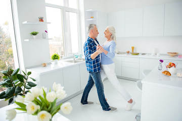 Side view full size, fullbody portrait of lovely stylish modern attractive creative couple in casual outfit dancing tango waltz in pair in the kitchen, enjoying morning, spending time together