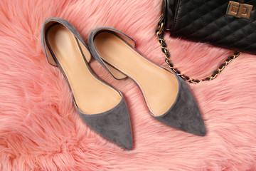 Elegant female shoes and bag on fluffy carpet
