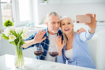 Portrait of lovely attractive stylish cheerful couple drinking red wine alcohol, shooting selfie on front camera, using smart phone, embracing, hugging, gesturing hello symbol, sign with palm