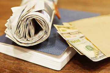 Rolled newspapers, business notebook and american dollars in cash on wooden table, close up