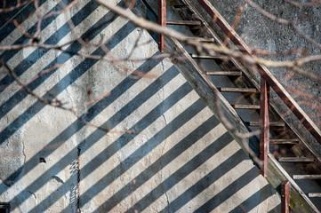 Schatten von Holzstiege auf Hausmauer